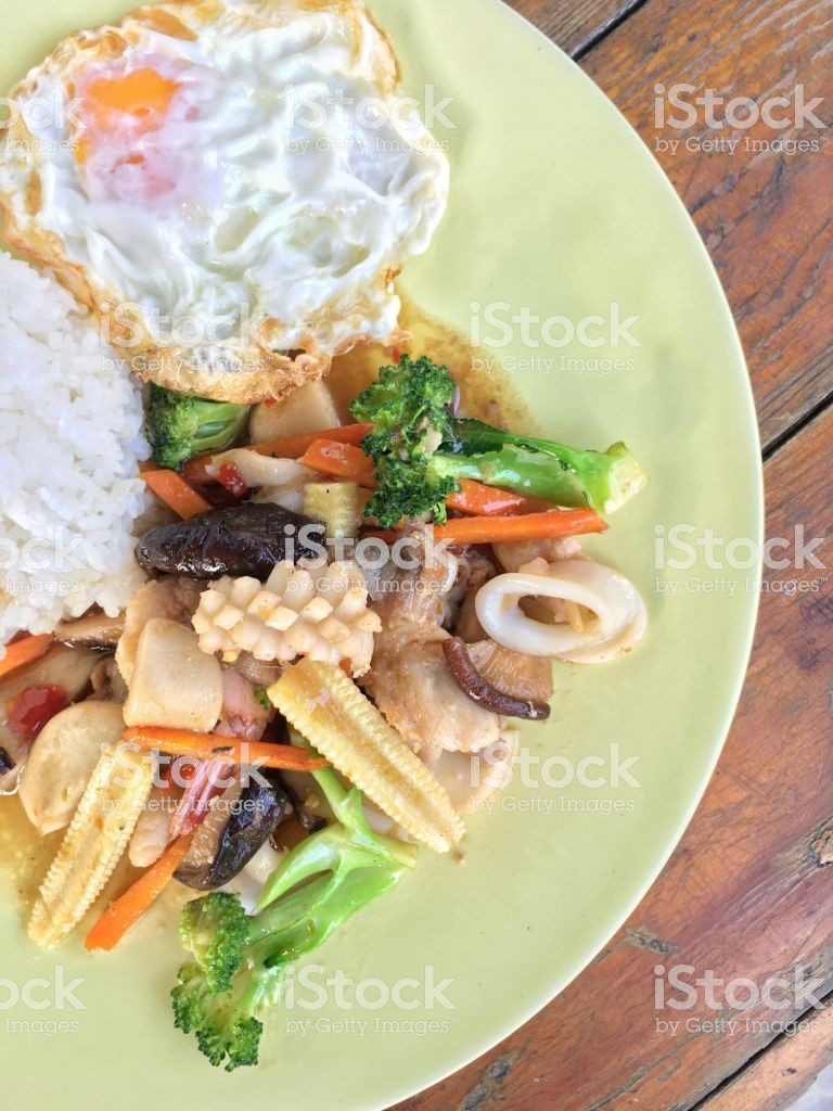 ve able stir fry in a plate on old wooden background with rice and picture id